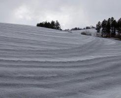 美瑛町の丘に融雪材がまかれて、春の畑仕事の準備をしている写真